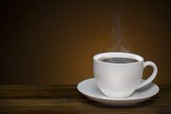 与烟-在木桌上的热的咖啡杯的无奶咖啡与co 免版税库存照片