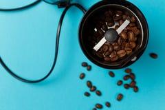 与烤咖啡豆的电磨咖啡器在与蓝色桌面的厨房用桌上 库存照片