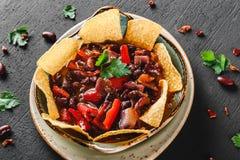 与烤干酪辣味玉米片或皮塔饼芯片的豆沙,胡椒和绿色在板材在黑暗的背景 墨西哥快餐,素食食物 库存照片