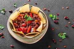 与烤干酪辣味玉米片或皮塔饼芯片的豆沙,胡椒和绿色在板材在黑暗的背景 墨西哥快餐,素食食物 库存图片