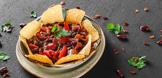 与烤干酪辣味玉米片或皮塔饼芯片的豆沙,胡椒和绿色在板材在黑暗的背景 墨西哥快餐,素食食物,顶视图, 免版税库存照片