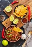 与烤干酪辣味玉米片用肉和芯片的辣豆汤在土气背景 墨西哥盘,顶视图 免版税库存图片