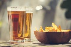 与烤干酪辣味玉米片的啤酒在一张木桌上切削 图库摄影
