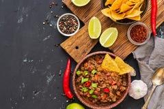 与烤干酪辣味玉米片的辣豆汤在土气背景切削 墨西哥食物 文本的,顶视图地方 免版税图库摄影