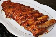 与烤肉或BBQ调味汁的被烘烤的排骨 免版税图库摄影