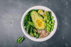 与烤菜和奎奴亚藜,菠菜,鲕梨,抱子甘蓝,夏南瓜,芦笋,编辑的绿色素食主义者菩萨碗沙拉 免版税库存图片