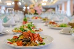 与烤菜的沙拉在餐馆 装饰的宴会桌 库存图片