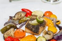 与烤菜的油煎的鳕鱼 库存图片