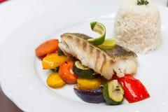 与烤菜的油煎的鳕鱼 免版税库存照片