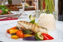 与烤菜的油煎的鳕鱼 免版税图库摄影