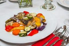与烤菜的油煎的鳕鱼 库存照片