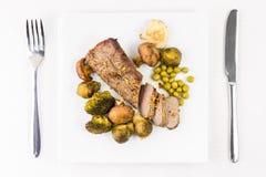 与烤菜的烤牛肉在服务的桌上 图库摄影