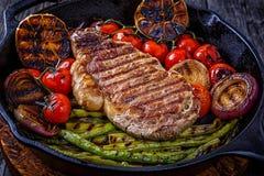 与烤菜的牛排在煎锅 库存照片
