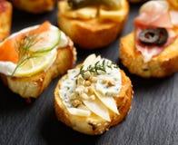 与烤长方形宝石的小点心增加青纹干酪、苹果切片、腰果和新鲜的麝香草在黑背景 图库摄影