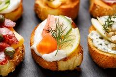 与烤长方形宝石的小点心用加法乳脂状的乳酪、熏制鲑鱼、黄瓜、柠檬和莳萝在黑背景 库存图片