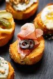 与烤长方形宝石的小点心用加法火腿和橄榄在黑背景 免版税库存图片