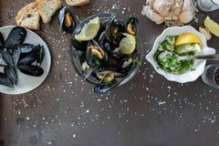 与烤面包片和鲜美调味汁的煮熟的可口黑淡菜 健康吃概念,蛋白质食物 库存图片