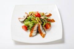 与烤鱼、蕃茄和搓碎干酪片断的沙拉莴苣  库存照片
