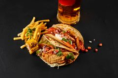 与烤鸡内圆角的第一个玉米粉薄烙饼,第二与鱼片,炸薯条、调味汁和啤酒在黑色 免版税库存图片