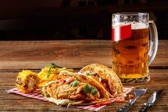 与烤鸡内圆角的第一个玉米粉薄烙饼,第二与鱼片,调味汁和啤酒在木桌上 图库摄影