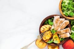 与烤鸡的在一个碗的沙拉和桃子有叉子的 健康的食物 顶视图 库存图片