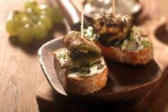 与烤滚动的鱼的食家敬酒的面包 免版税库存图片