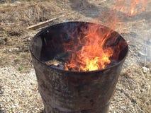 与烧与明亮的火焰的被点燃的垃圾的金属桶 免版税库存照片