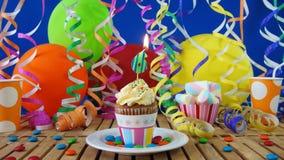 与烧在土气木桌上的蜡烛的生日6杯形蛋糕 免版税库存照片