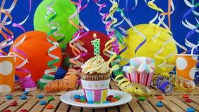 与烧在土气木桌上的蜡烛的生日1杯形蛋糕 库存图片