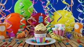 与烧在土气木桌上的蜡烛的生日5杯形蛋糕 免版税库存照片