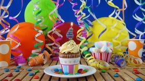与烧在土气木桌上的蜡烛的生日4杯形蛋糕 库存照片