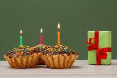 与烧欢乐蜡烛和礼物盒的生日杯形蛋糕在绿色背景 库存图片