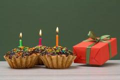 与烧欢乐蜡烛和礼物盒的生日杯形蛋糕在绿色背景 免版税库存照片