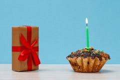 与烧欢乐蜡烛和礼物盒的鲜美生日杯形蛋糕有蓝色背景 免版税库存照片