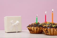 与烧欢乐蜡烛的礼物盒和生日杯形蛋糕在淡紫色背景 免版税图库摄影