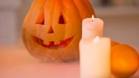 与烧照亮的可怕面孔的微笑的被雕刻的万圣夜南瓜蜡烛 股票录像