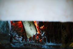 与烧红色炭烬的木头的壁炉 免版税库存照片