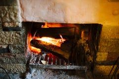 与烧红色炭烬的木头的壁炉 图库摄影