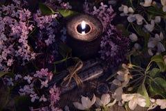 与烧黑蜡烛的淡紫色春天花 库存照片