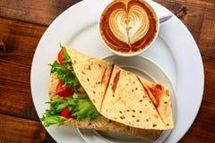 与热奶咖啡和三明治的早餐 免版税库存图片