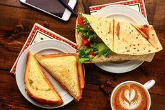 与热奶咖啡和三明治的早餐 图库摄影