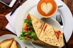 与热奶咖啡和三明治的早餐 库存照片
