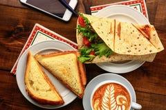 与热奶咖啡和三明治的早餐 库存图片