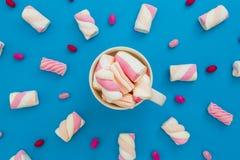 与热奶咖啡杯子和糖果的五颜六色的蛋白软糖在桃红色背景 平的位置,顶视图 图库摄影