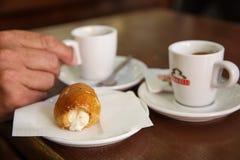与热奶咖啡的意大利酥皮点心 免版税库存照片