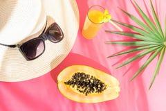 与热带水果汁番木瓜棕榈叶的草帽太阳镜高玻璃在紫红色的背景 阳光泄漏 katya krasnodar夏天领土假期 库存图片