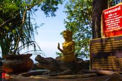 与热带的特写镜头的一个小金黄菩萨雕象 在菩萨寺庙的小雕象在泰国 库存图片