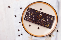 与热心的巧克力和在白色桌上的咖啡豆 库存照片