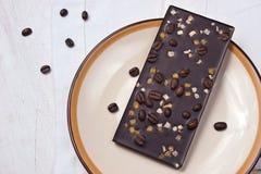 与热心的巧克力和在白色桌上的咖啡豆 免版税库存照片