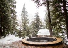 与热水的陈水池在多雪的山 库存图片